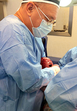 Dr Szőcs Gyula újszülöttel a műtöben